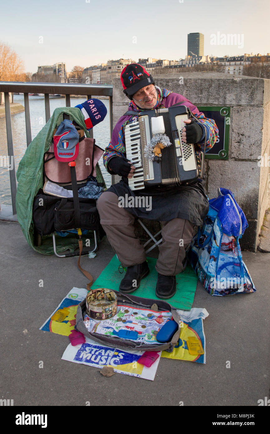 On a cold winter day a street musician playing an accordion for spare change on Pont Saint Louis in Paris, France. - Stock Image