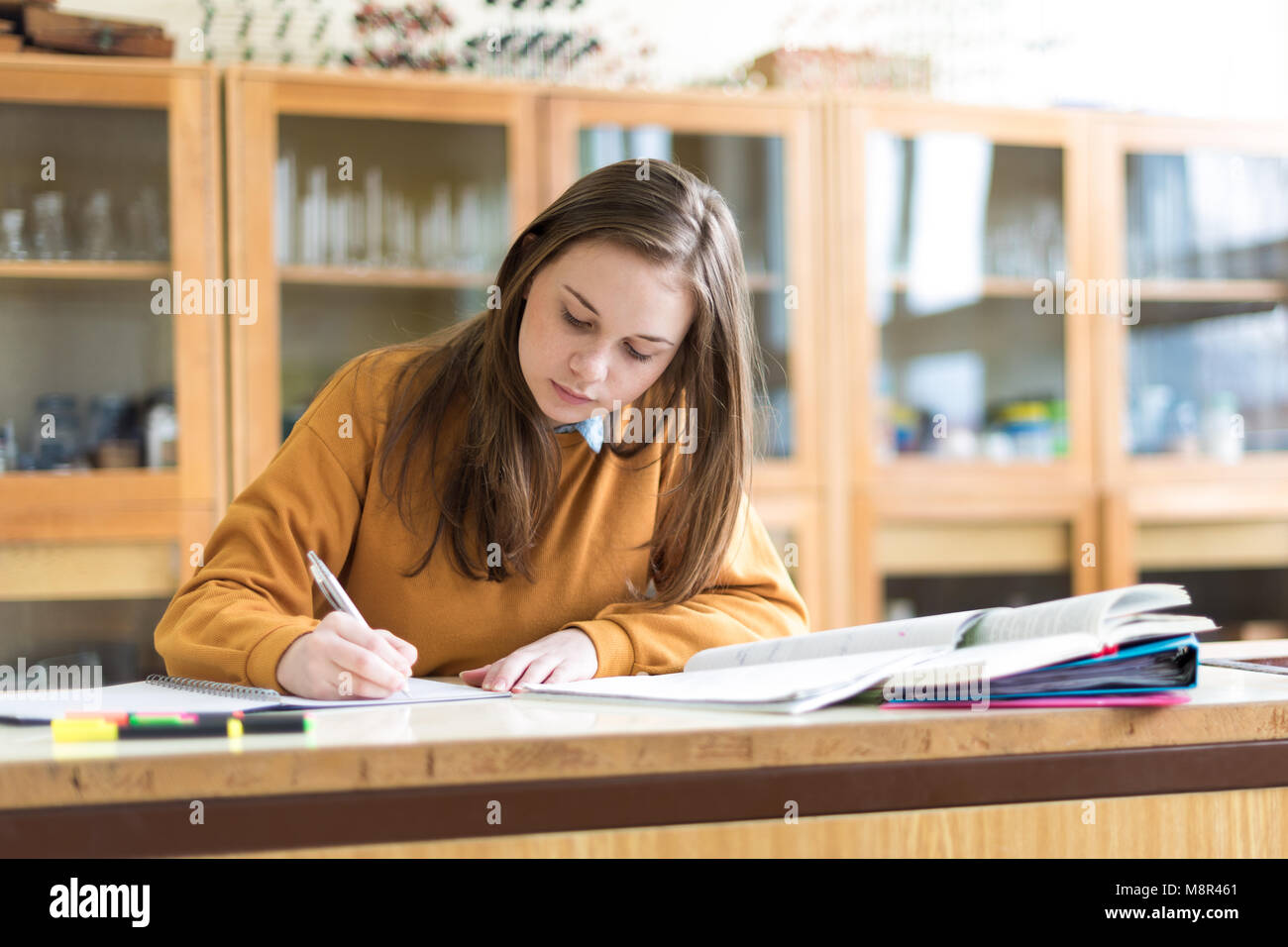 Young female college student in chemistry class, writing notes. Focused student in classroom. Authentic Education Stock Photo