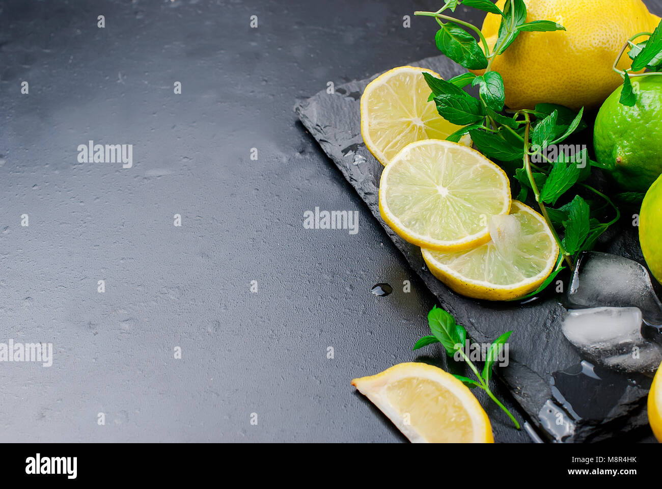 Top view of ice cubes and mojito cocktail ingredients on black slate board, cocktail drinks concept - Stock Image