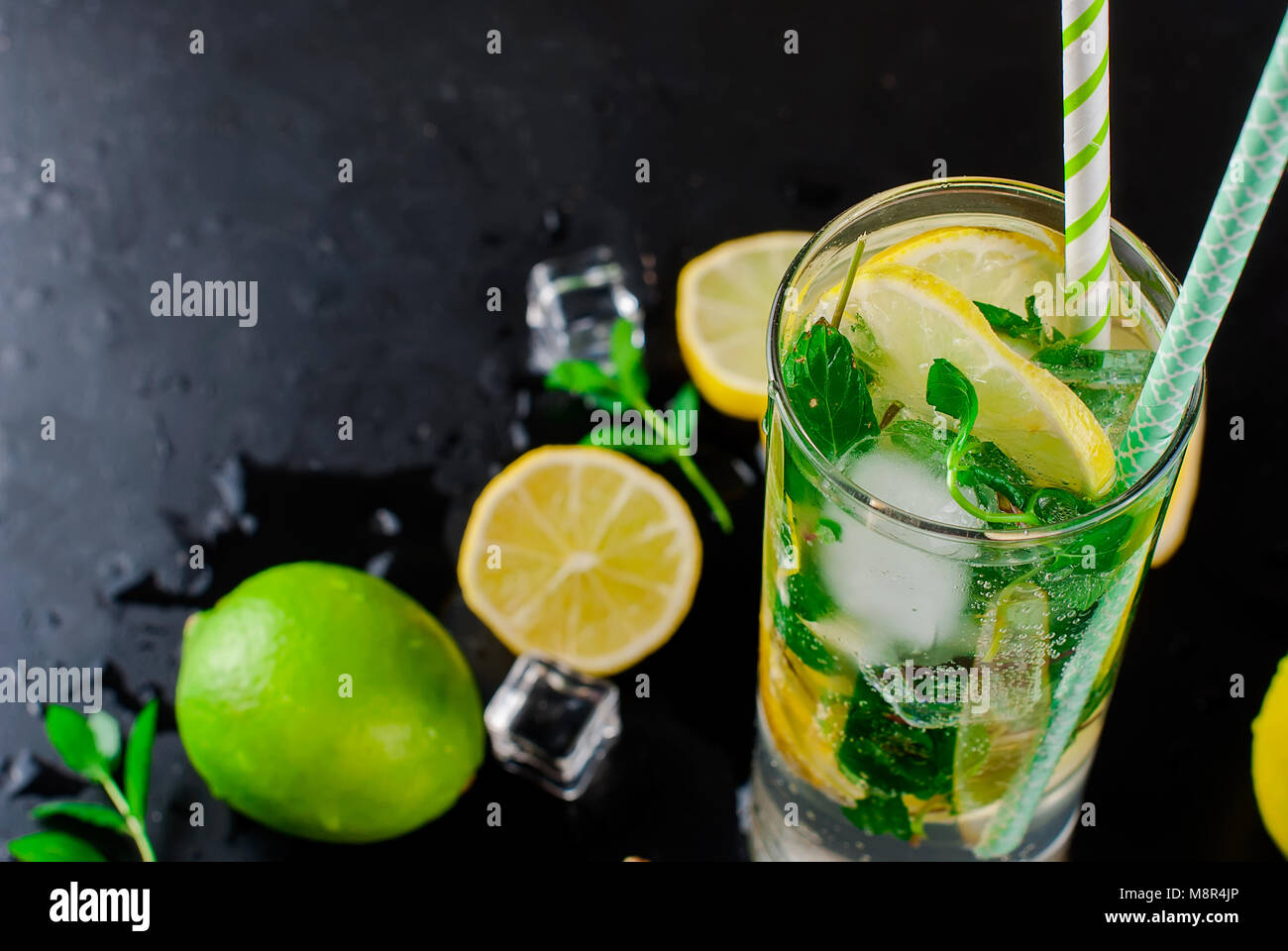 Top view of mojito cocktail, ice cubes and  cocktail ingredients on black slate board, cocktail drinks concept - Stock Image