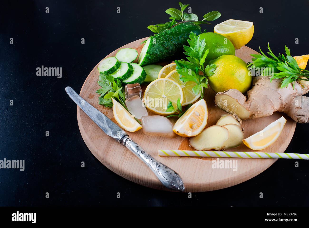 ingredients for refreshing cucumber cocktail, lemonade, detox water on a black background. Top view. Copy space. - Stock Image