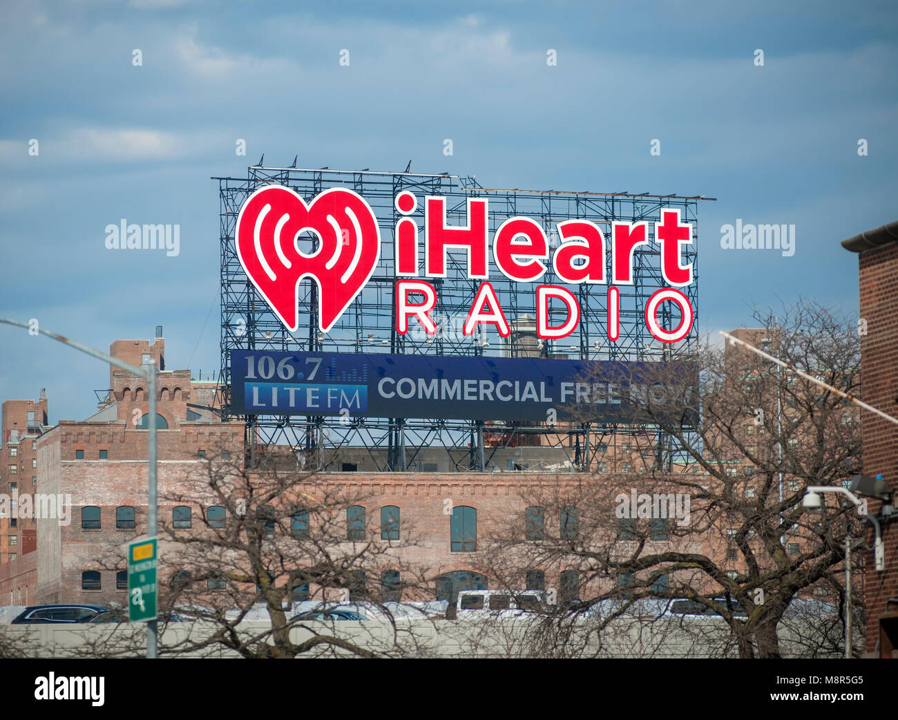 A giant billboard in the Bronx, in New York faces Manhattan and advertises iHeartMedia on Thursday, March 15, 2018. - Stock Image