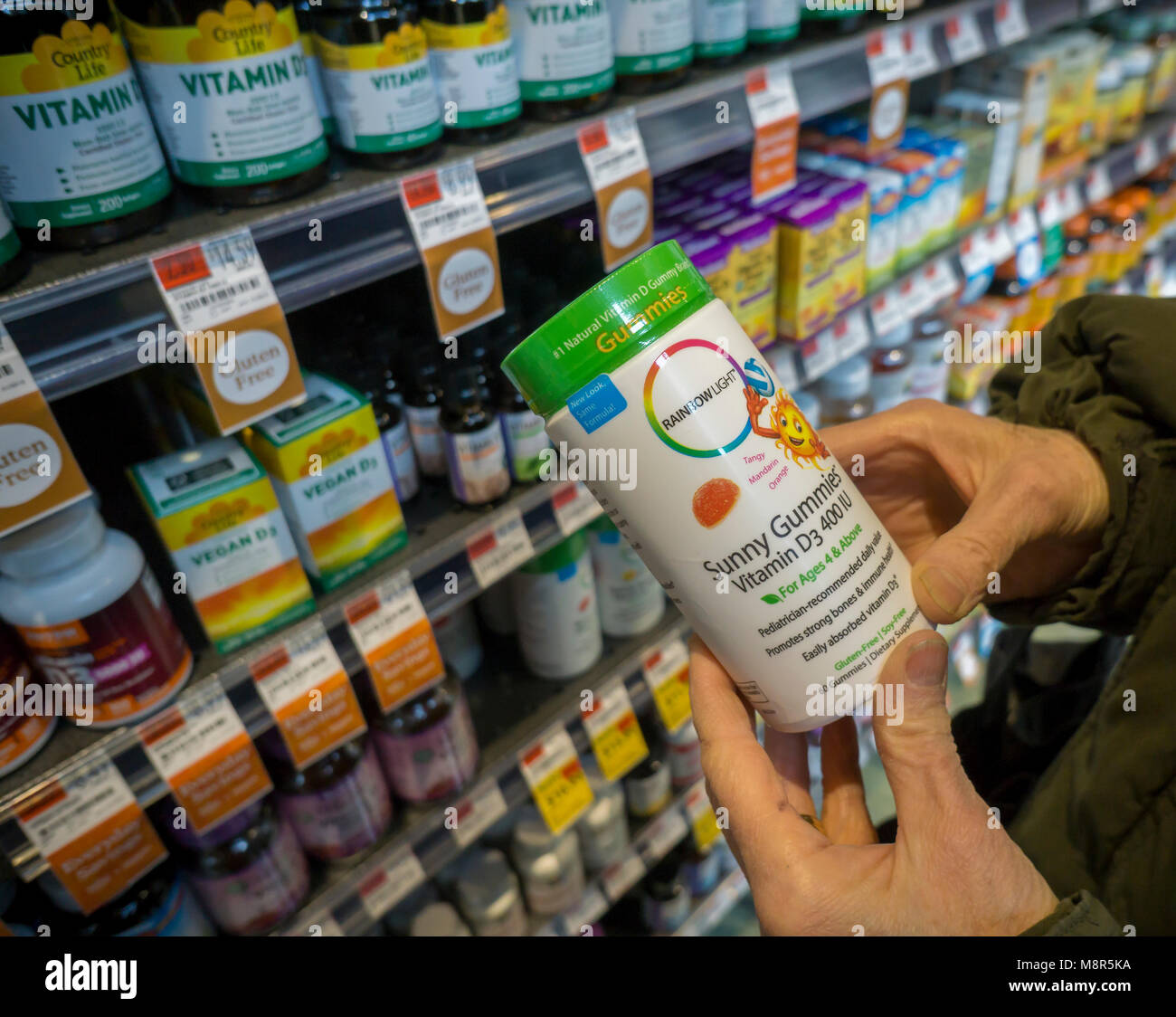 A consumer chooses a jar of Rainbow Light vitamin supplement in a store in New York on Monday, March 12, 2018. The - Stock Image