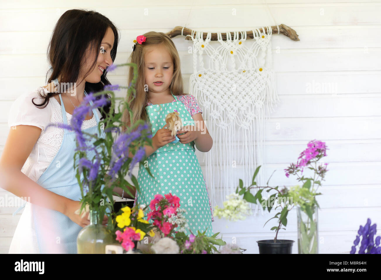 Florist girl who creates a bouquet of flowers standing on a wooden table - Stock Image