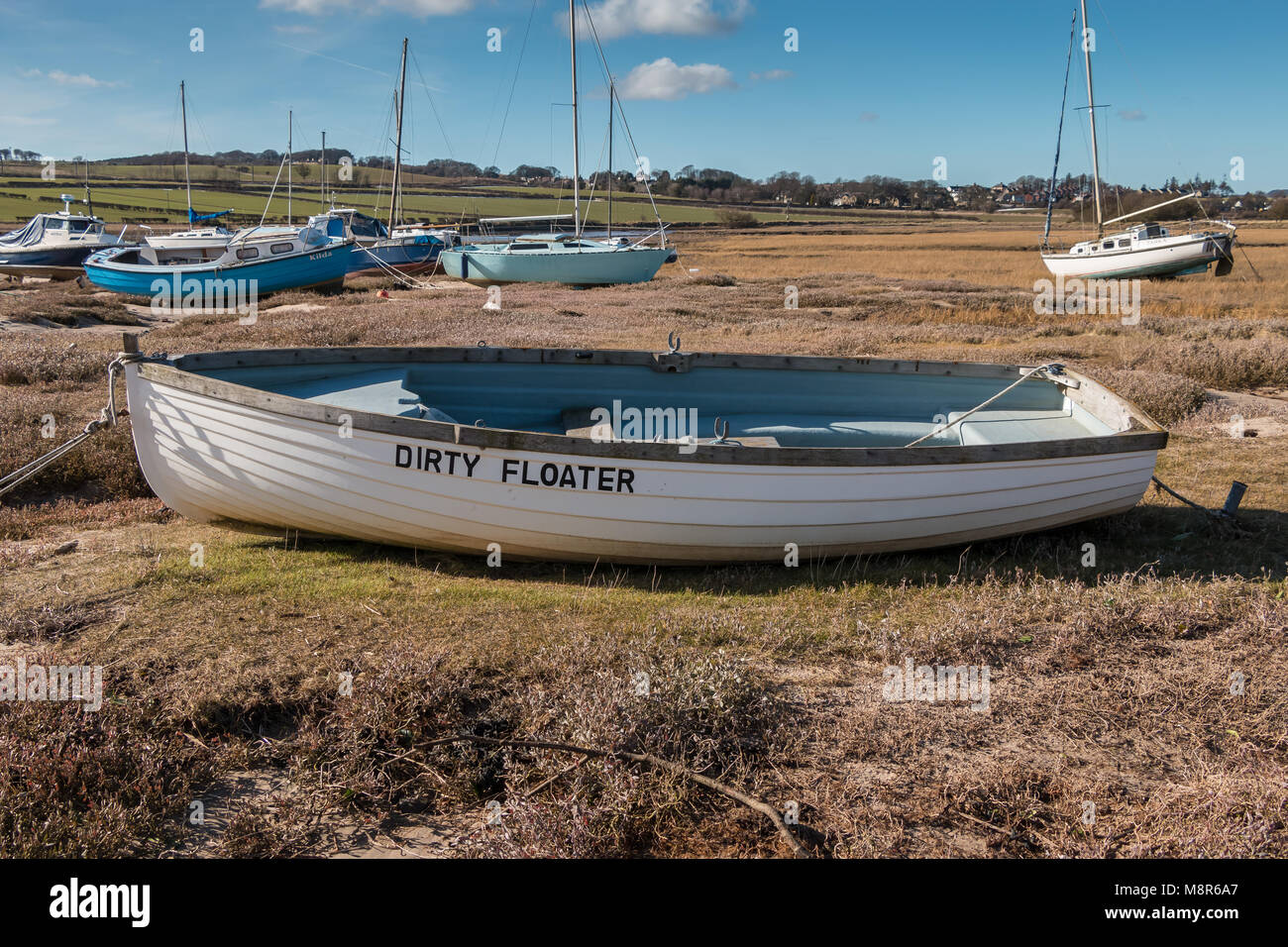 Dinghy with amusing name Dirty Floater moored in Alnmouth Harbour, Northumberland Coast AONB, at low tide with other - Stock Image