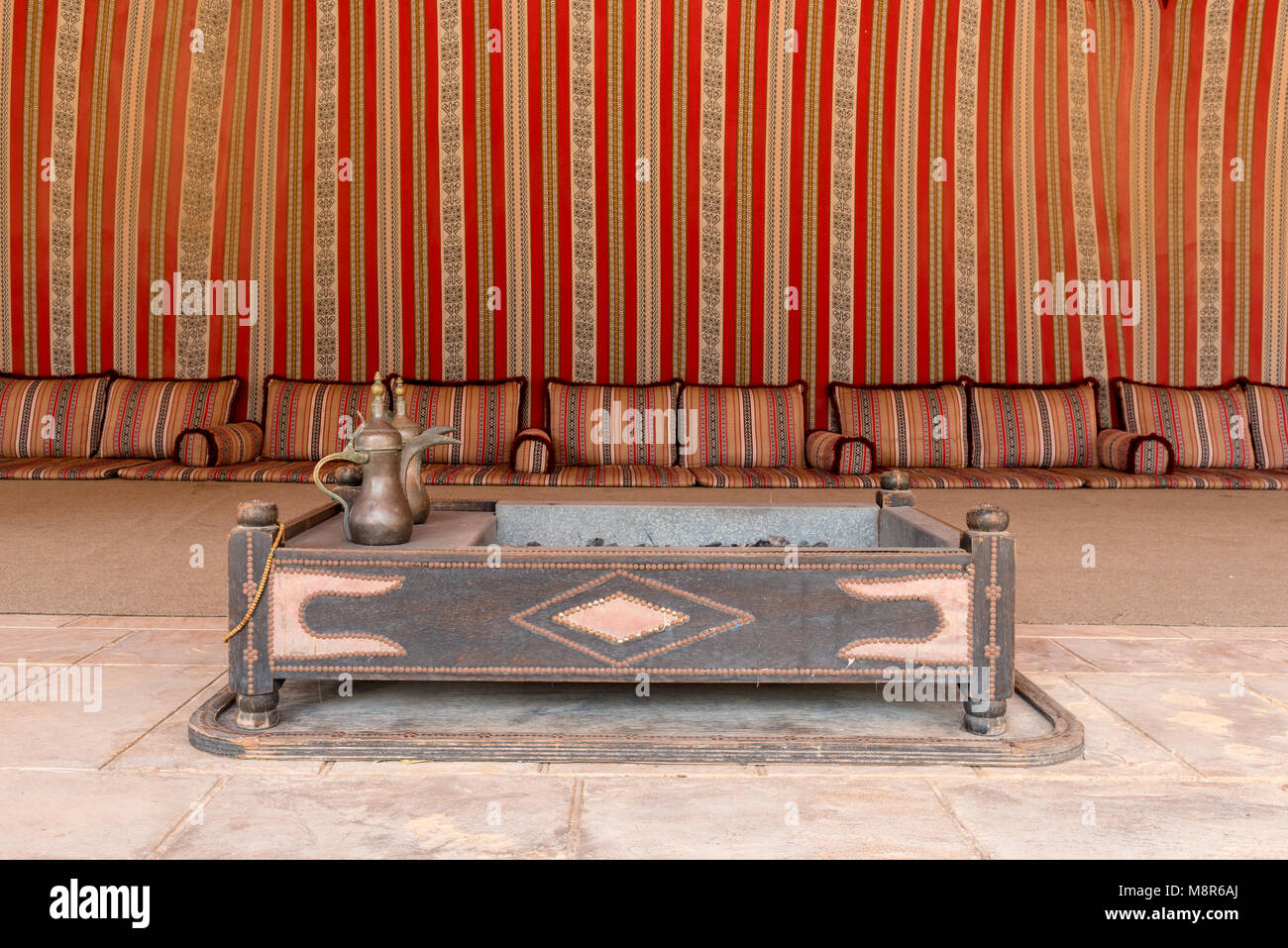 Interior of a large traditional arab tent lined with red patterned woven fabric and the floor covered in cushions - Stock Image