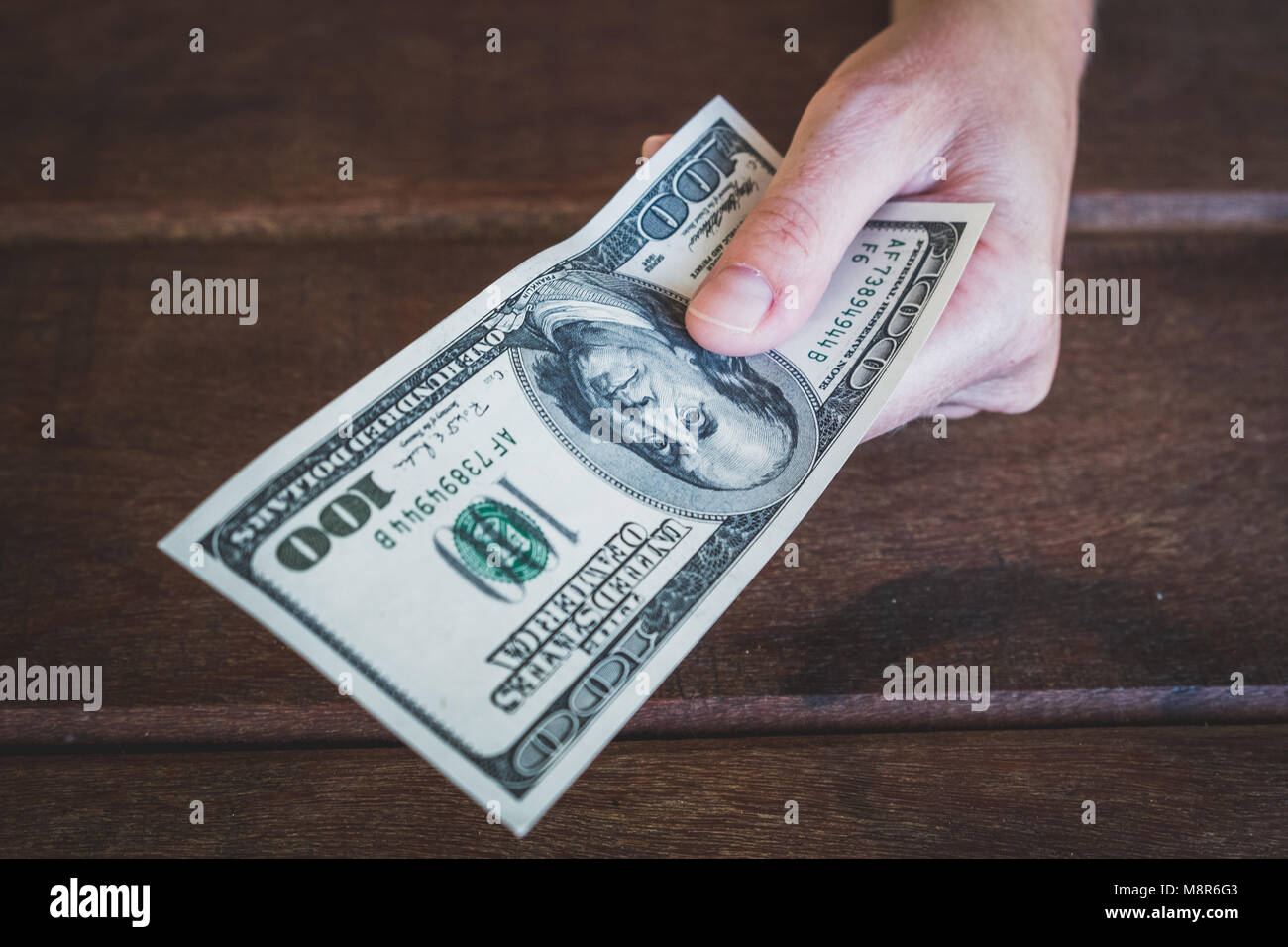 hundred dollars -  hand  holding 100 dollar bill - Stock Image