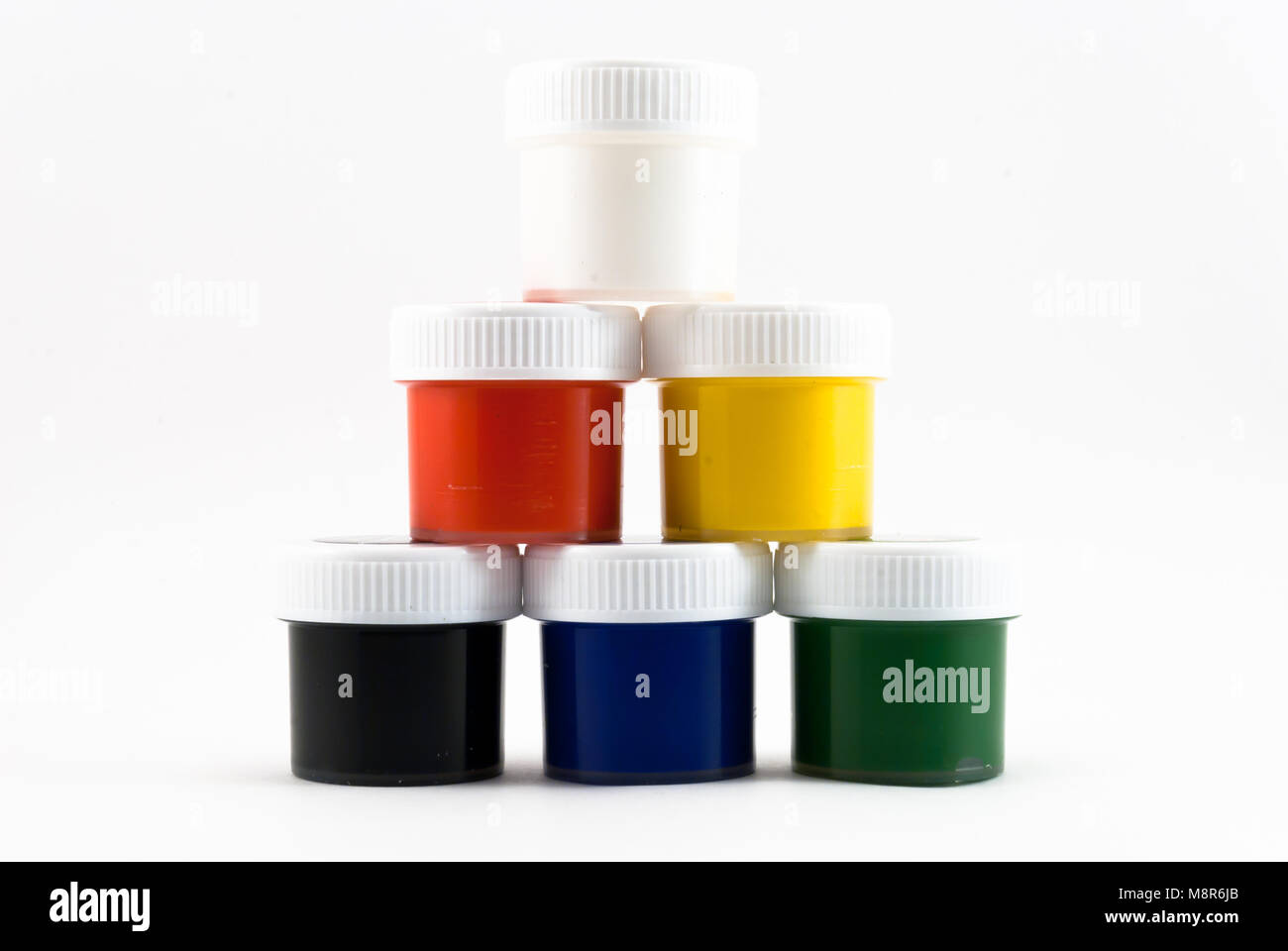 Few watercolor gouache paints in pyramid on white background - Stock Image