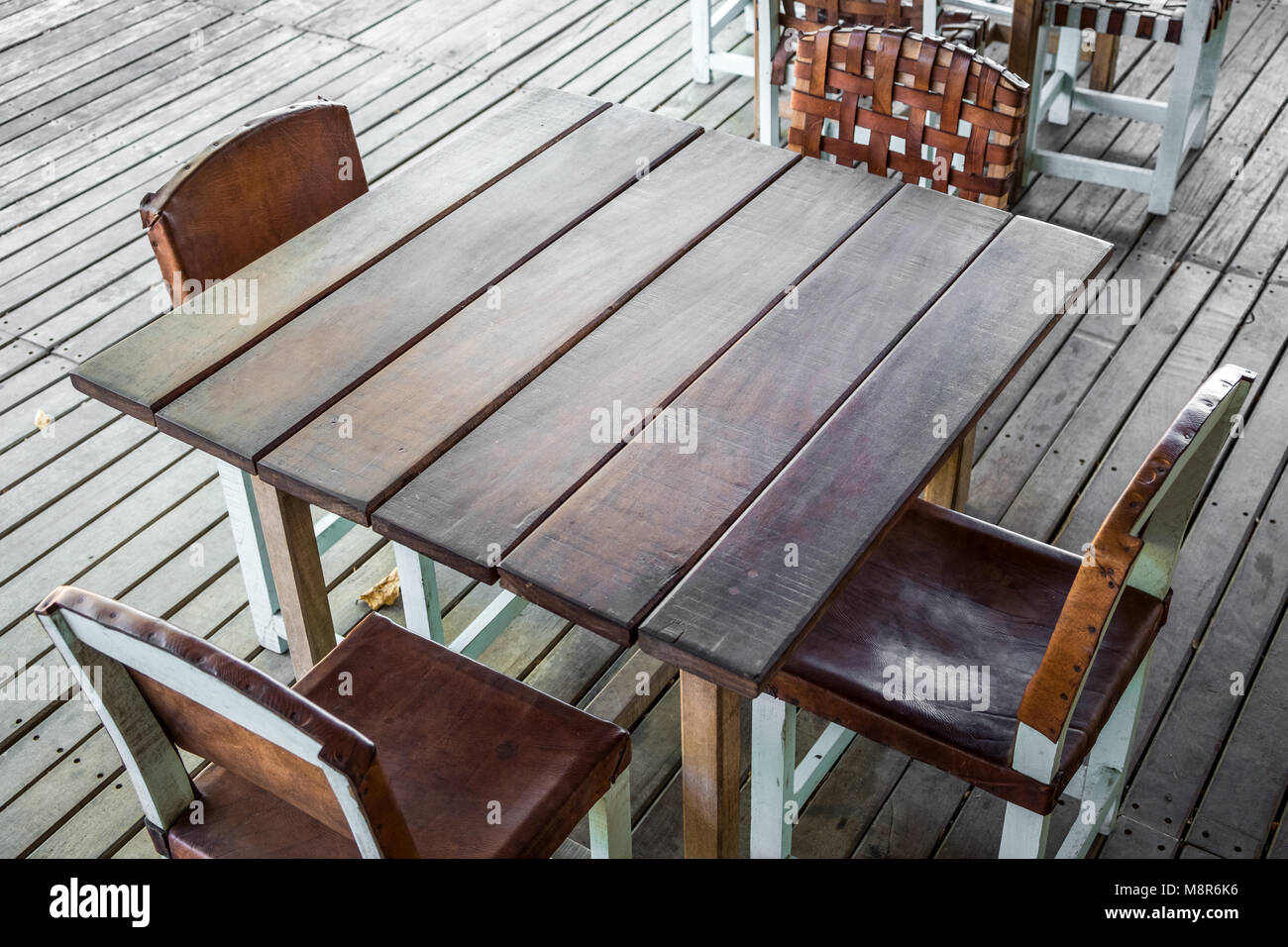 empty wooden table in restaurant with four empty chairs - vintage furniture - - Stock Image