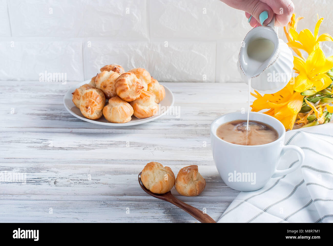 Breakfast, a cup of coffee and eclairs, flowers on a white background - Stock Image