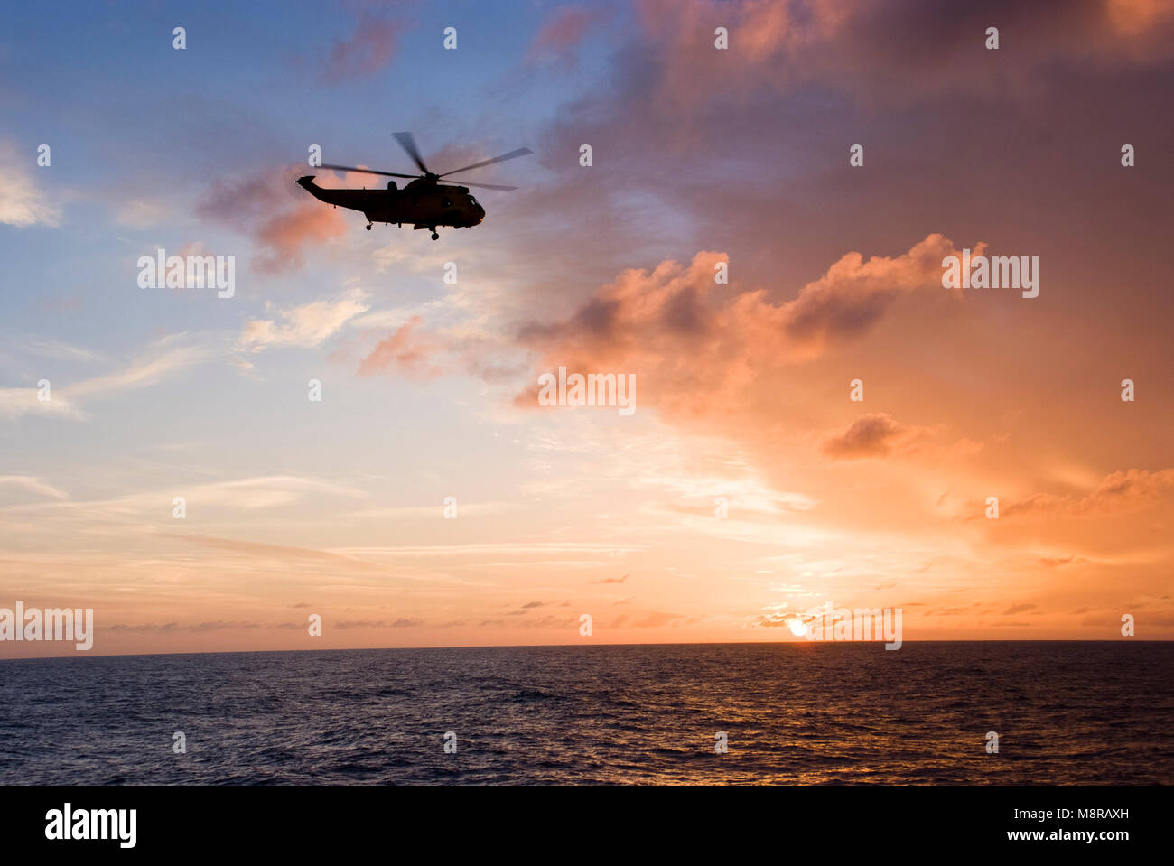 Silhouette of helicopter flying into sunset Stock Photo