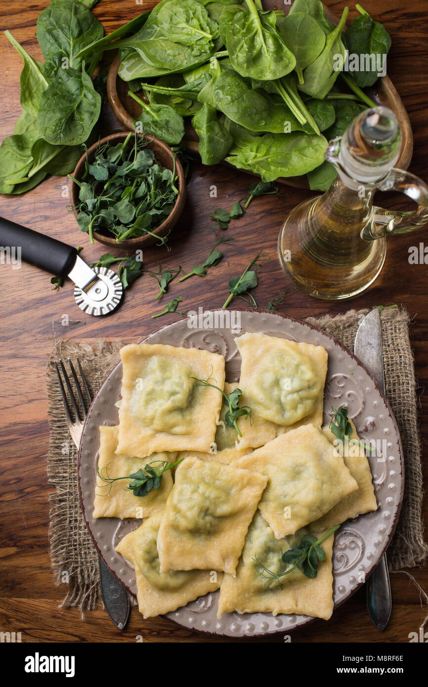 ready ravioli in a plate, spinach, olive oil in a jar. - Stock Image