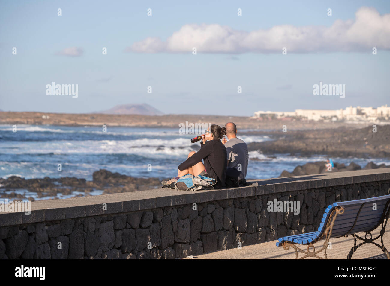 Young couple drinking while contemplating the sea in La Santa, Lanzarote, Canary Islands, Spain - Stock Image