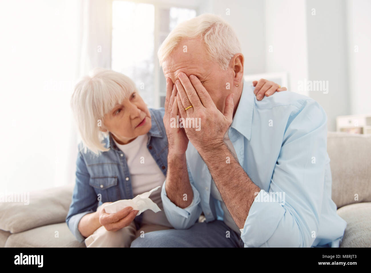 Loving wife consoling her sobbing husband - Stock Image