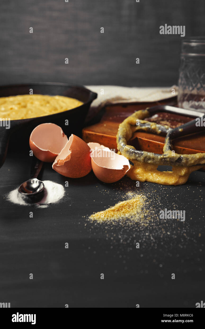 Close-up of messy kitchen counter with broken eggshells and kitchen utensils - Stock Image