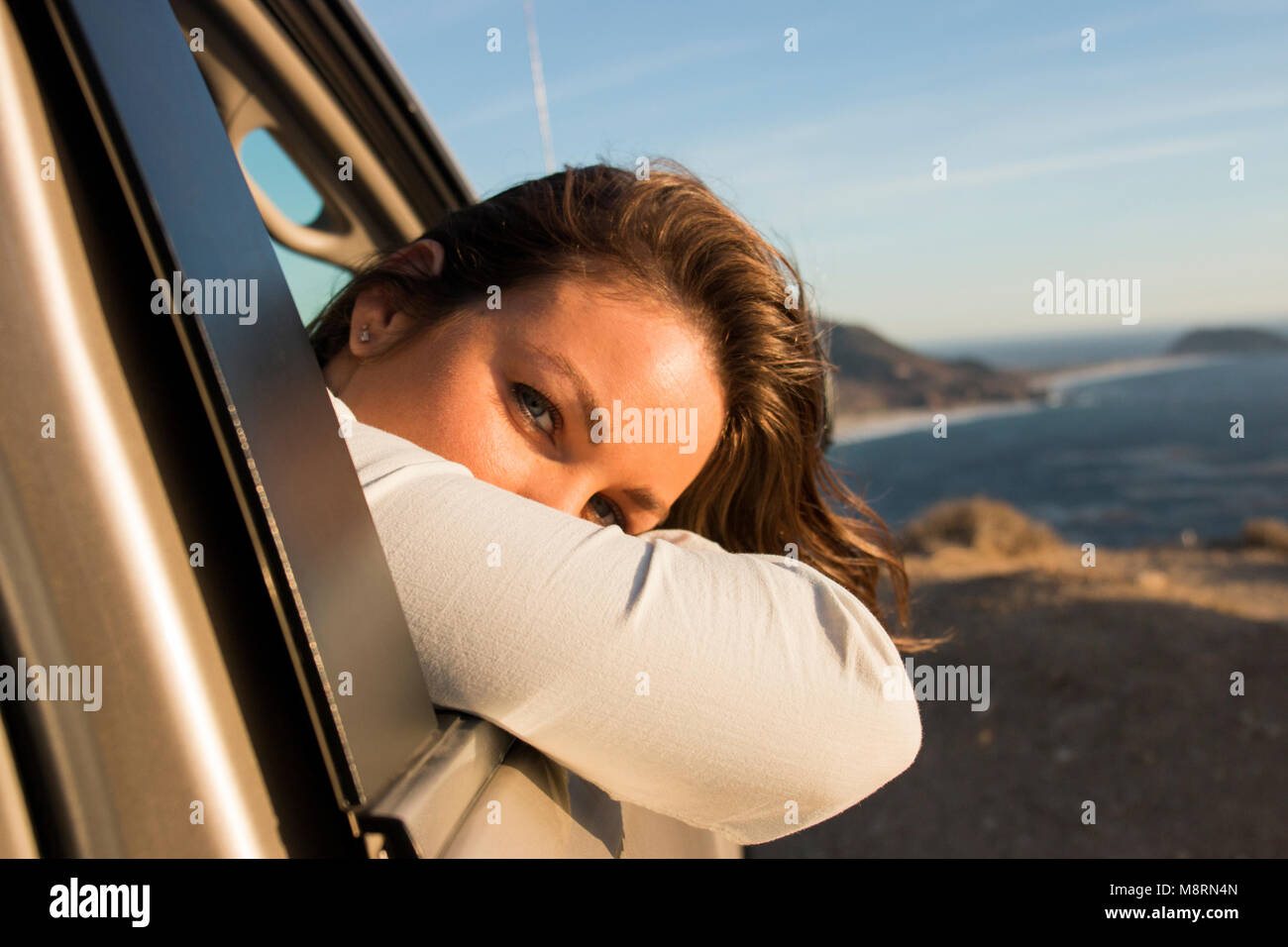 Portrait of woman looking through car window at beach against sky during sunset Stock Photo