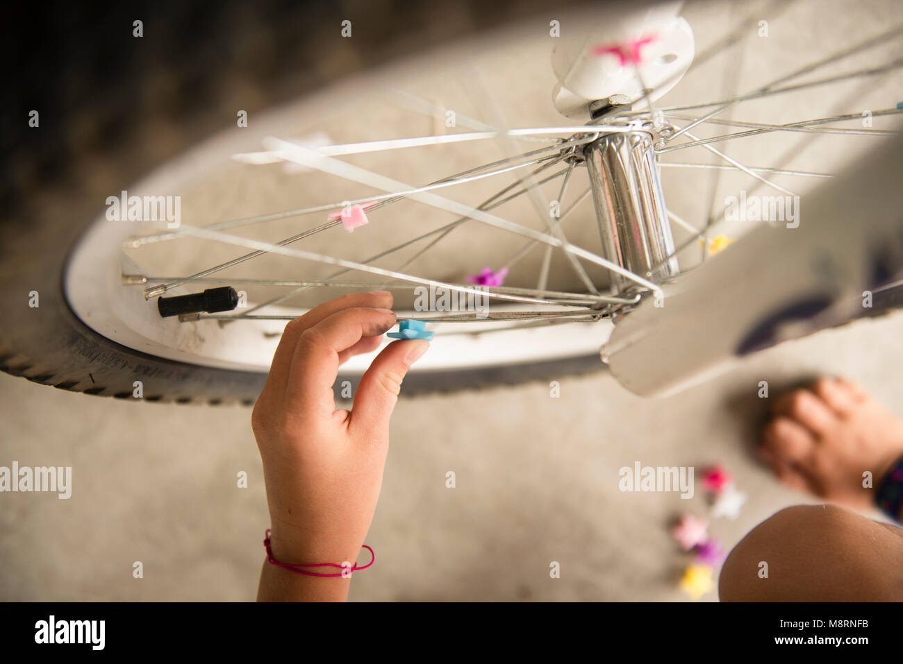 Cropped image of girl decorating bicycle tire - Stock Image
