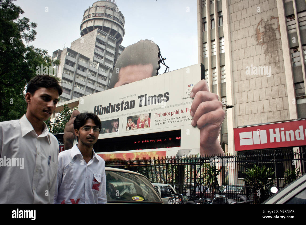 New Delhi, India: Two young Indians pass in front of the Hindustan times in New Delhi - Stock Image