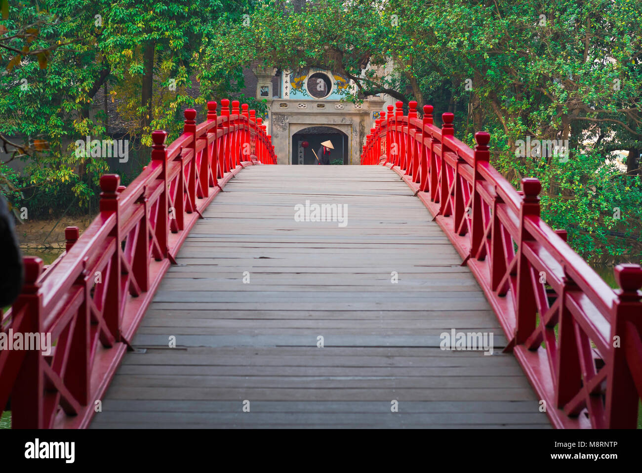 Hanoi bridge, across the Huc Bridge in Hanoi a woman sweeps the entrance to the Temple Of The Jade Mound on Hoan - Stock Image