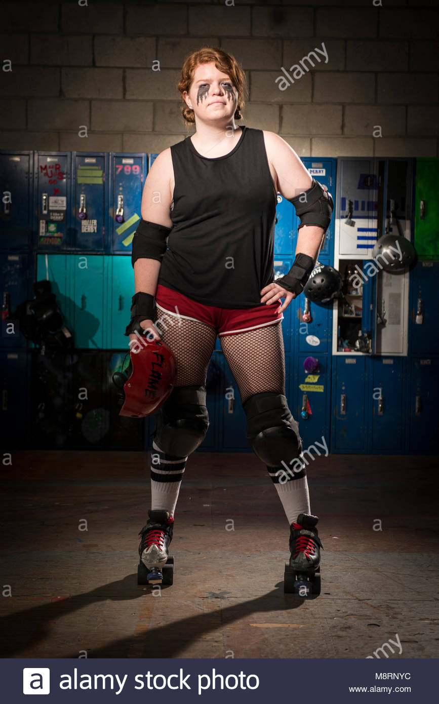 Portrait of confident sportswoman with hand on hip wearing roller skates while standing against lockers - Stock Image