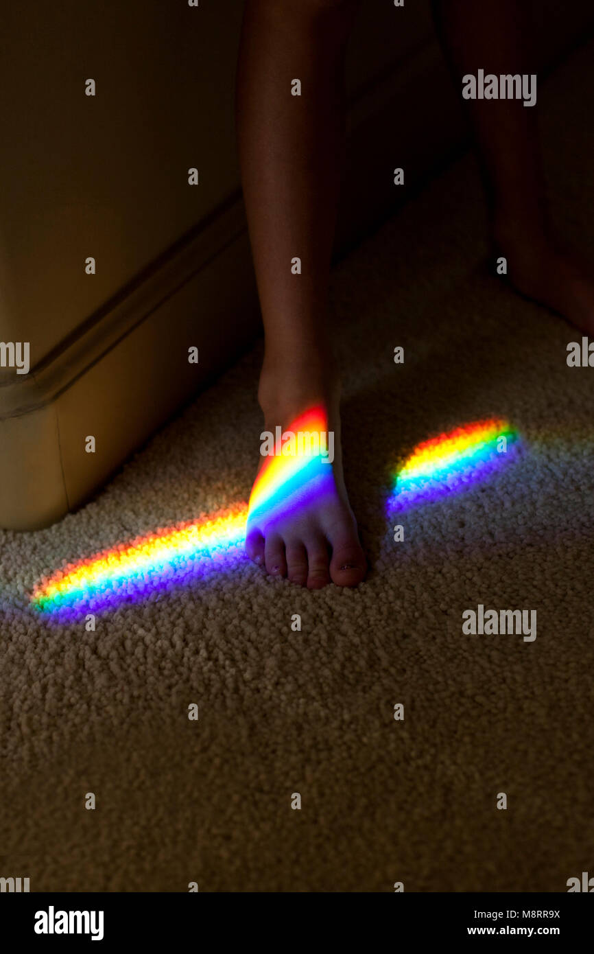 High angle view of prism falling on girl legs at home - Stock Image