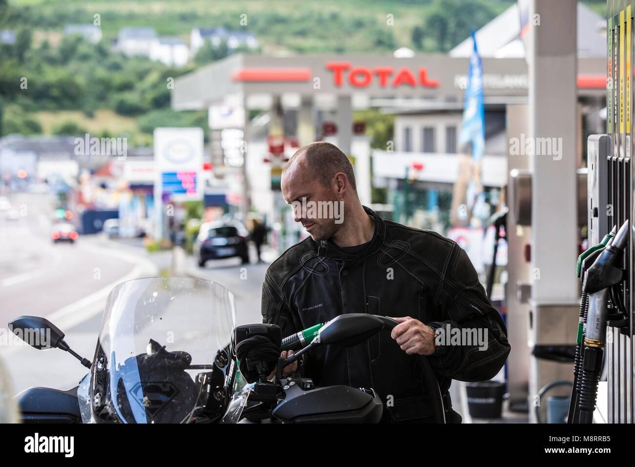 Ein junger Mann tankt sein Motorrad in Martelange an der belgisch-luxemburgischen Grenze. Hier kostet der Sprit - Stock Image