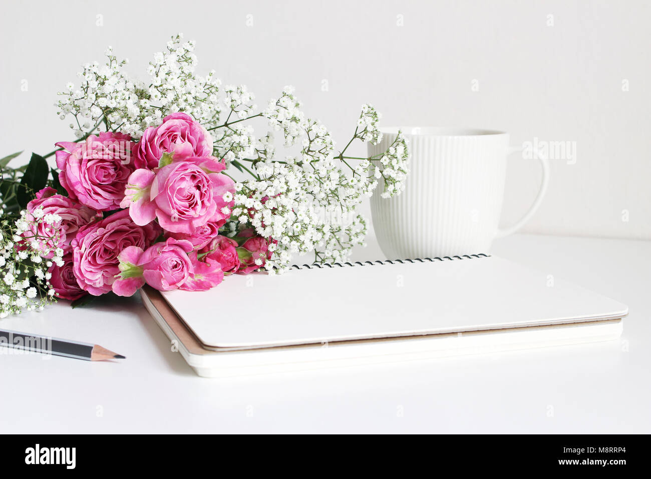 Styled stock photo. Closeup of wedding bouquet made of pink roses and baby's breath, Gypsophila flowers lying on Stock Photo