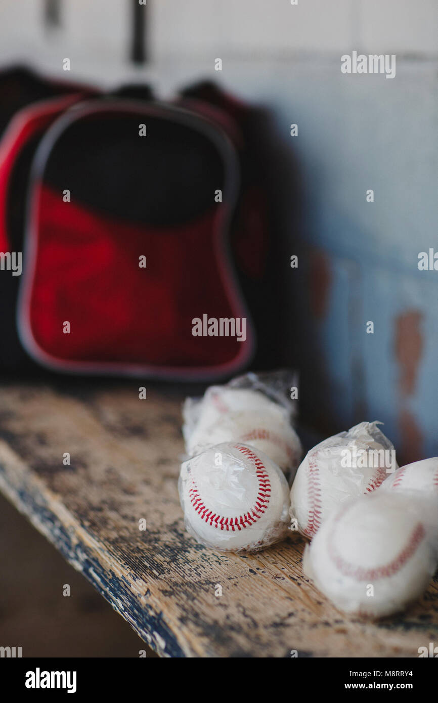 Close-up of baseball balls on wooden table in sports dugout - Stock Image