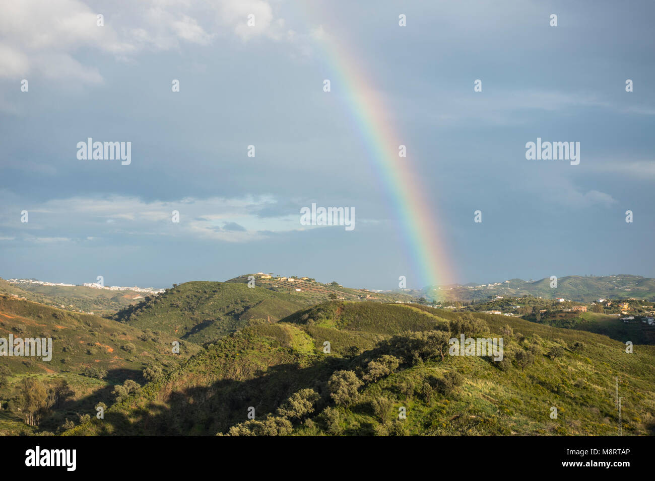 Rainbow over rolling hills of Andalusian Countryside, Malaga, Costa del Sol, Spain. - Stock Image