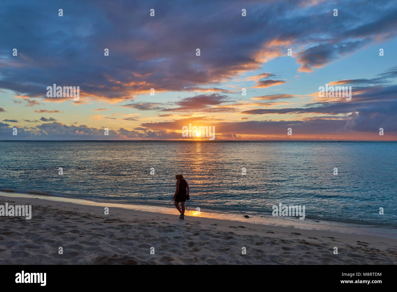 A Woman walking along Le Morne Beach on the Island of Mauritius at Sunset one Summers evening. - Stock Image