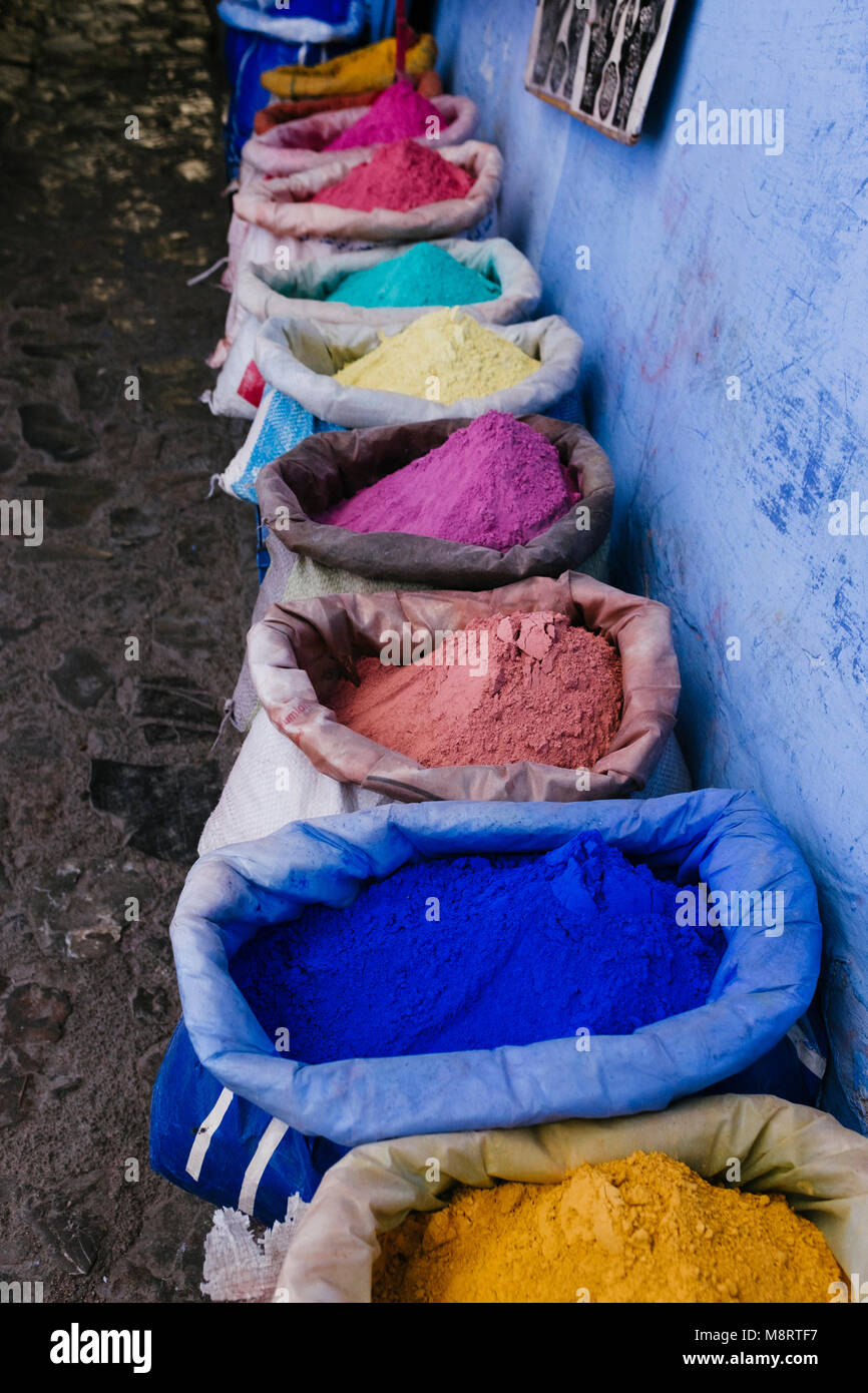 High angle view of colorful powder paints in sacks for sale by wall - Stock Image