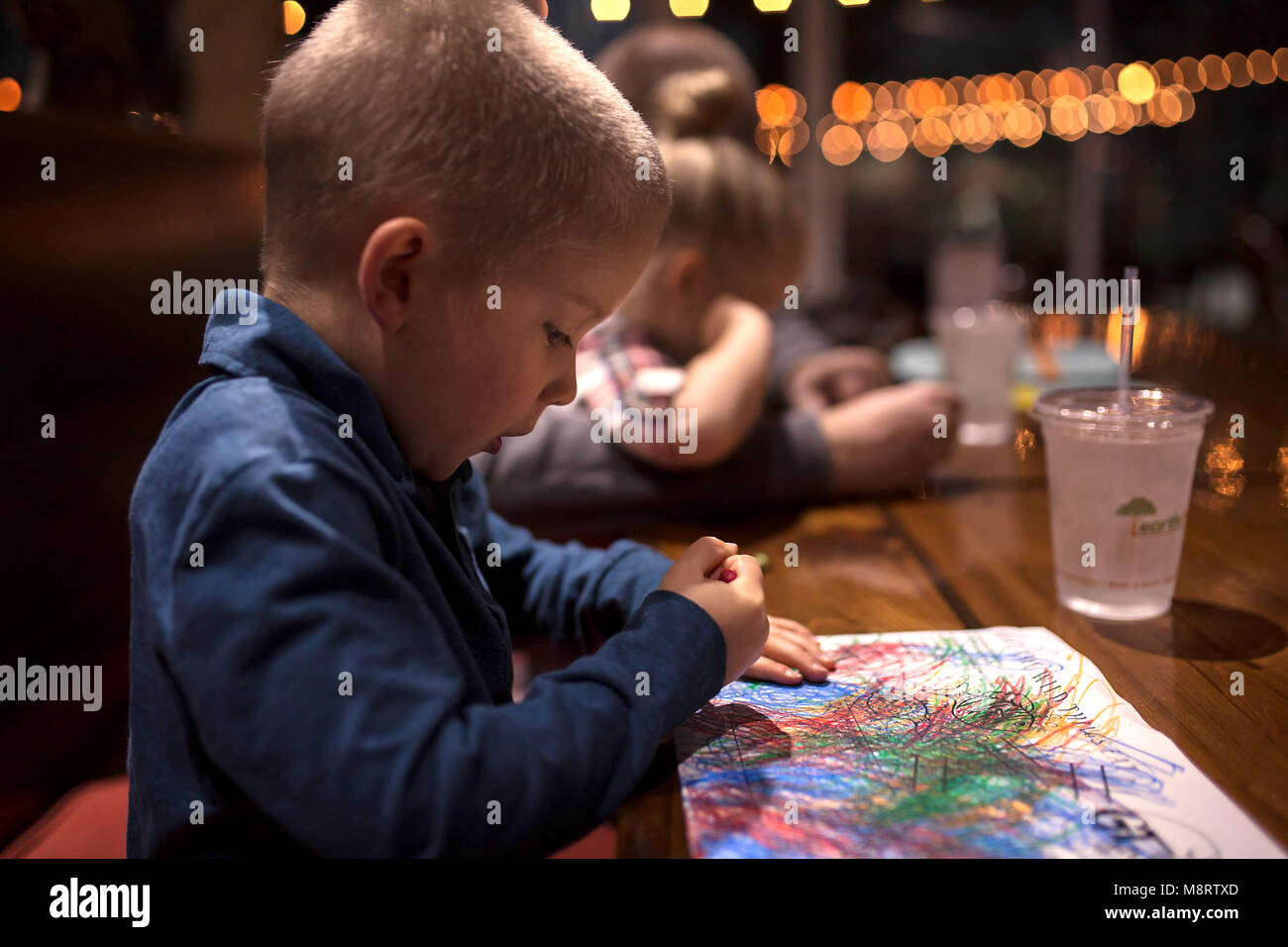 Side view of boy coloring on paper at dining table in restaurant - Stock Image
