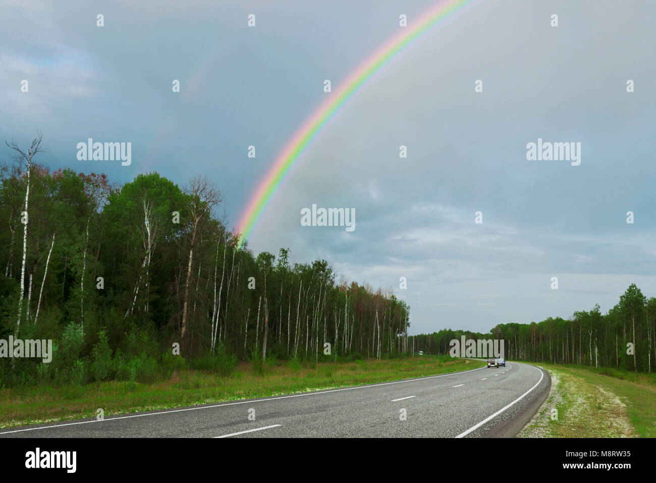 Rainbow after rain over highway in the summer Stock Photo