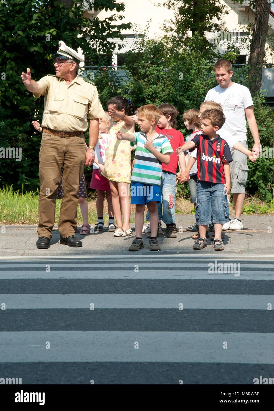 Polizist fürt Kinder über die Strasse. Kinder im Strassenverkehr - Stock Image