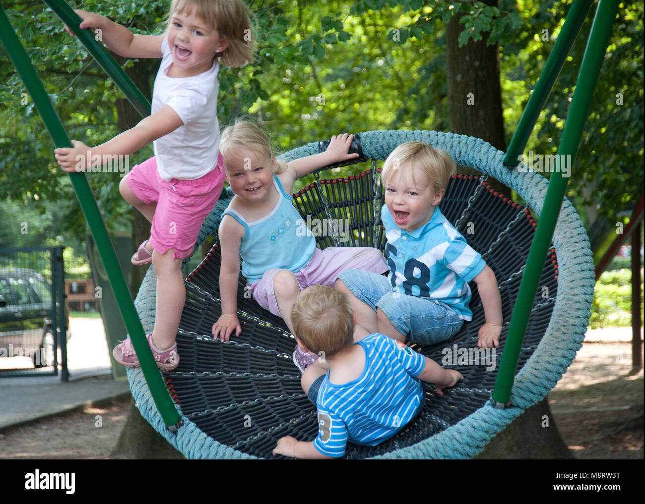 Katholischer, integrativer Kindergarten 'St. Maria - Frieden'   Kinder schaukeln - Stock Image