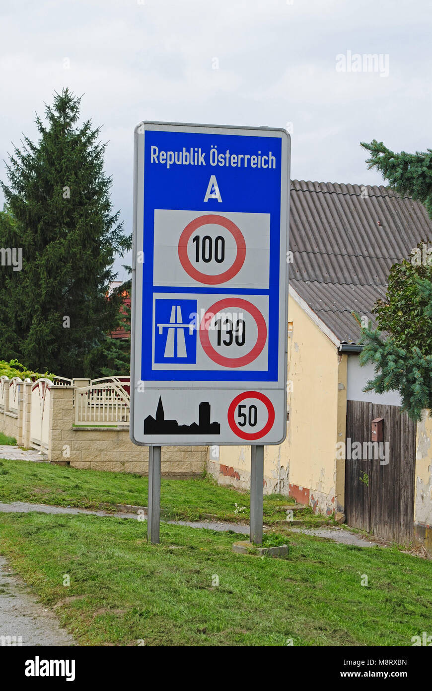 A speed limit sign welcomes the visitors at the border in Austria. - Stock Image