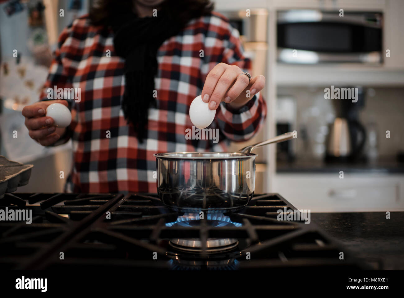 Midsection of woman putting eggs in container on illuminated stove - Stock Image
