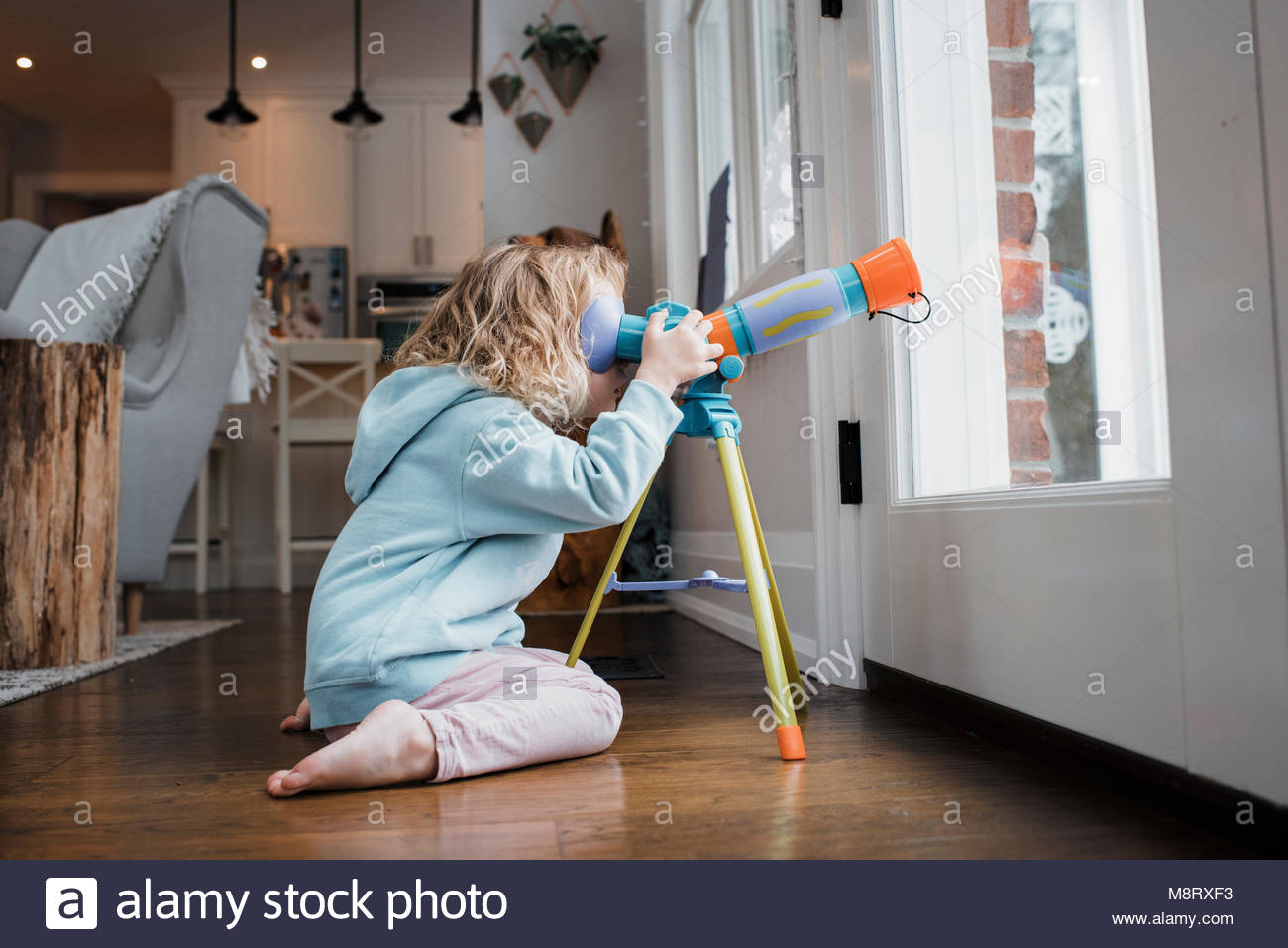 Side view of girl looking through telescope while kneeling by door at home - Stock Image