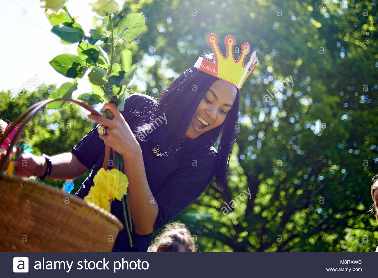 960e82e768cdb Happy woman wearing paper crown while carrying basket during birthday  celebration at backyard - Stock Image