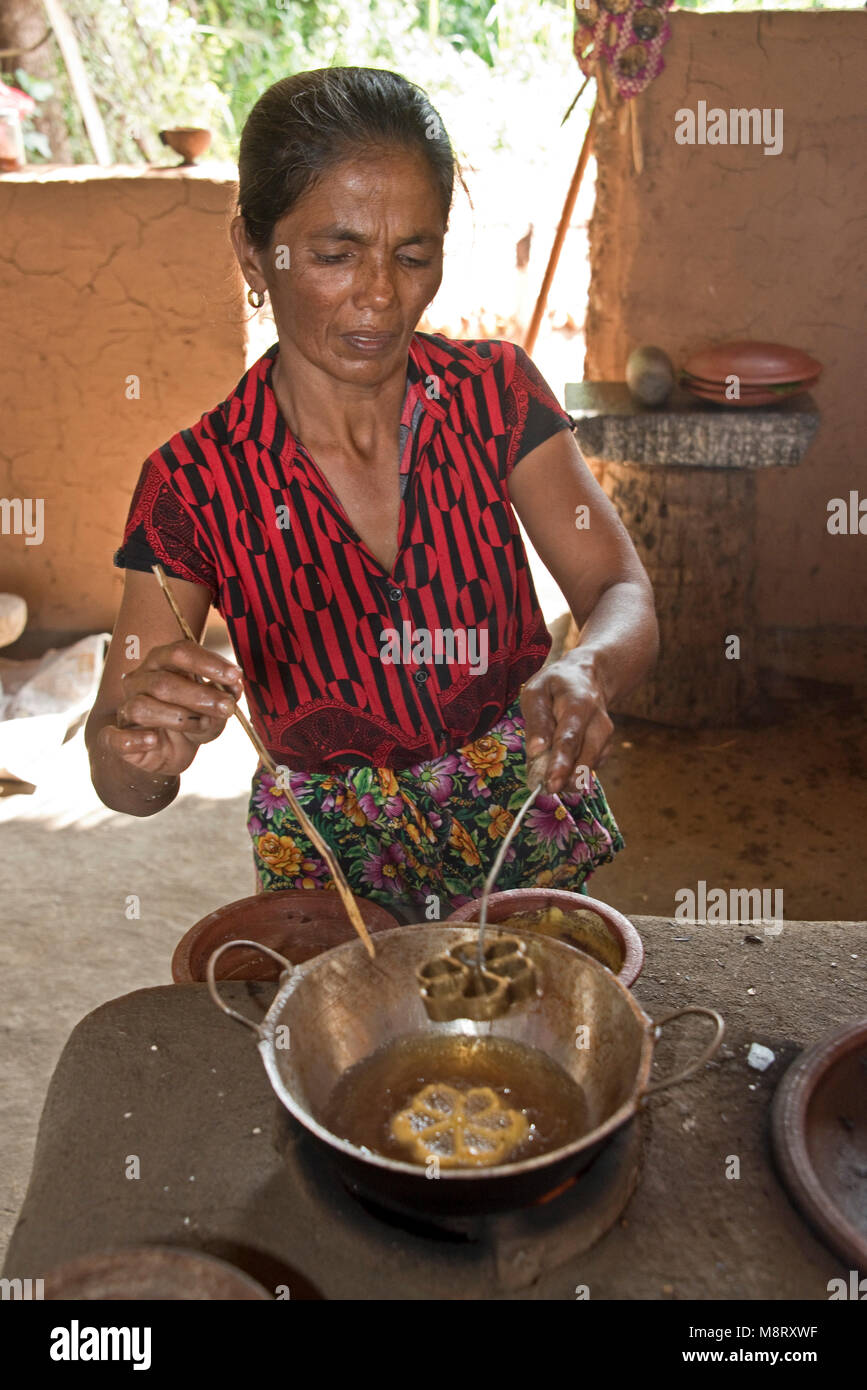 A friendly local Sri Lankan woman preparing traditional food (Kokis) at her home, a small farm just outside Sigiriya. - Stock Image
