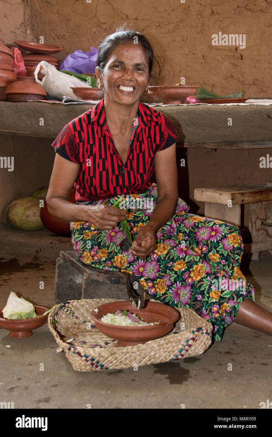 A friendly local Sri Lankan woman preparing traditional food at her home - a small farm just outside Sigiriya. - Stock Image
