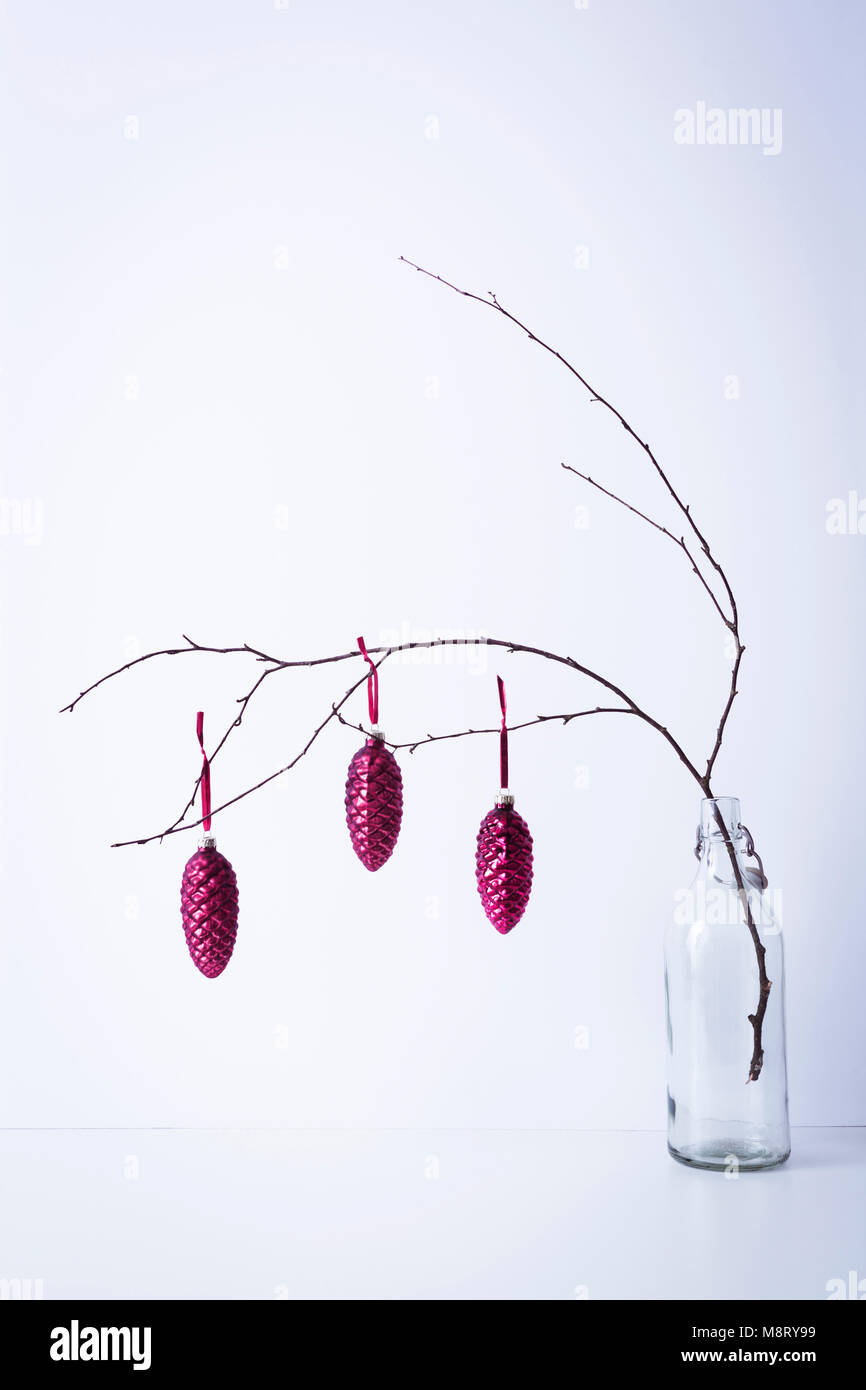 Christmas decorations hanging on twig in bottle against white background - Stock Image