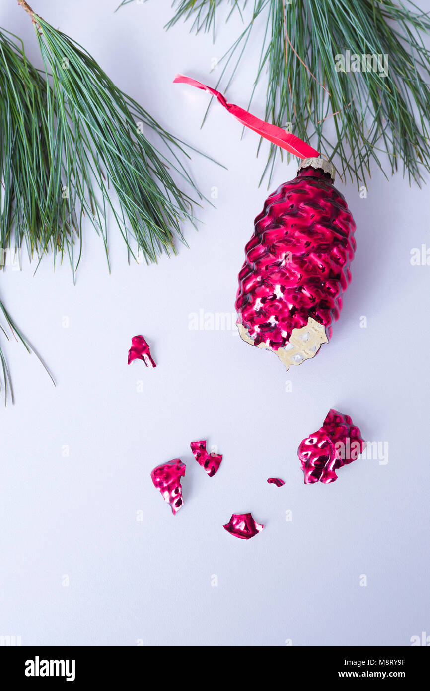 Close-up of broken Christmas Decoration with pine needles over white background - Stock Image