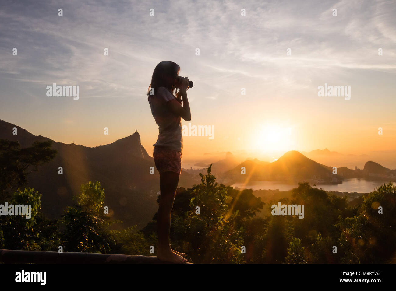 Girl Taking pictures of sunrise in Vista Chinesa, Rio de Janeiro, Brazil Stock Photo