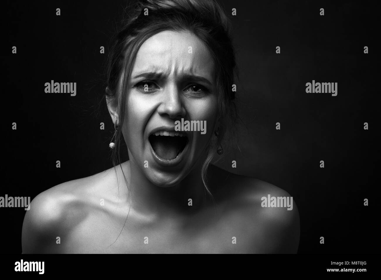young angry woman on black background screaming on camera, monochrome - Stock Image