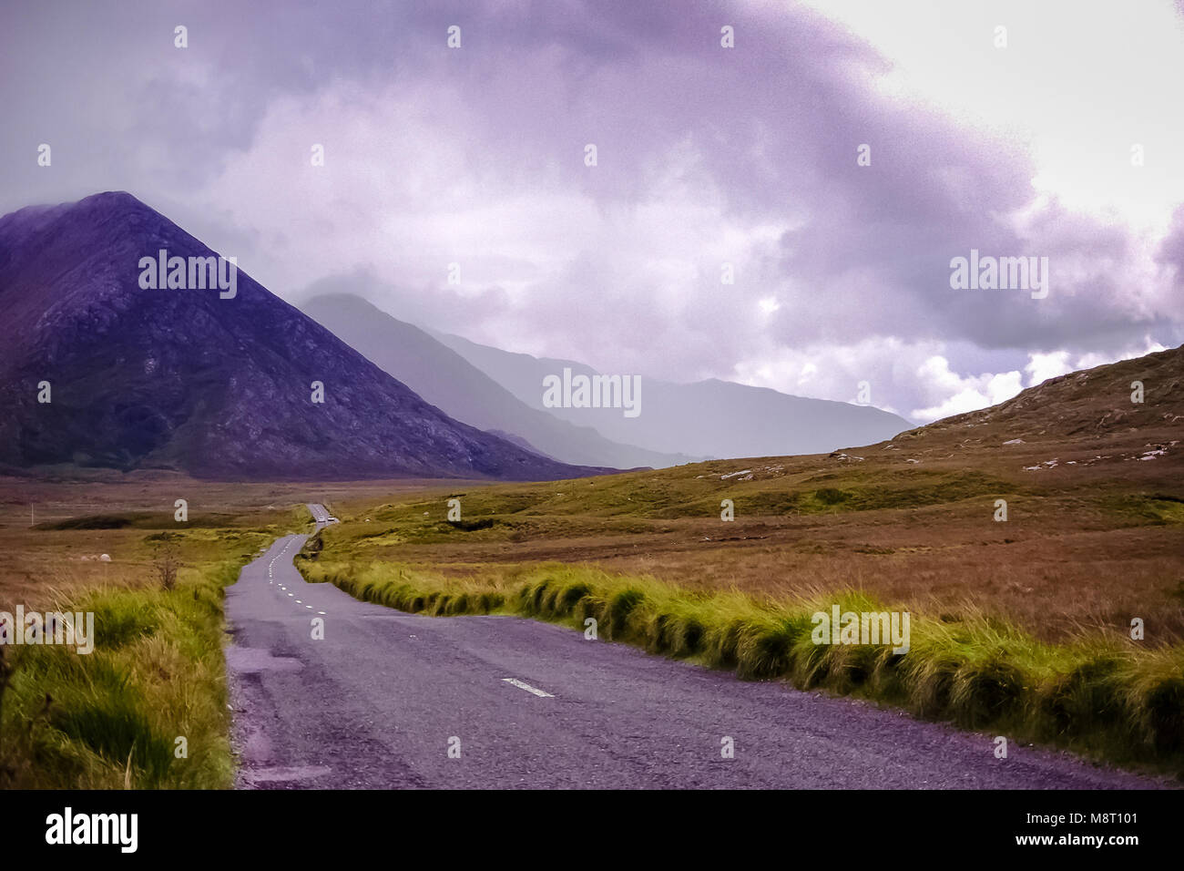 The Twelve the Twelve Bens (Na Beanna Beola) mountain range in the background. Winding road, stormy skies - Stock Image