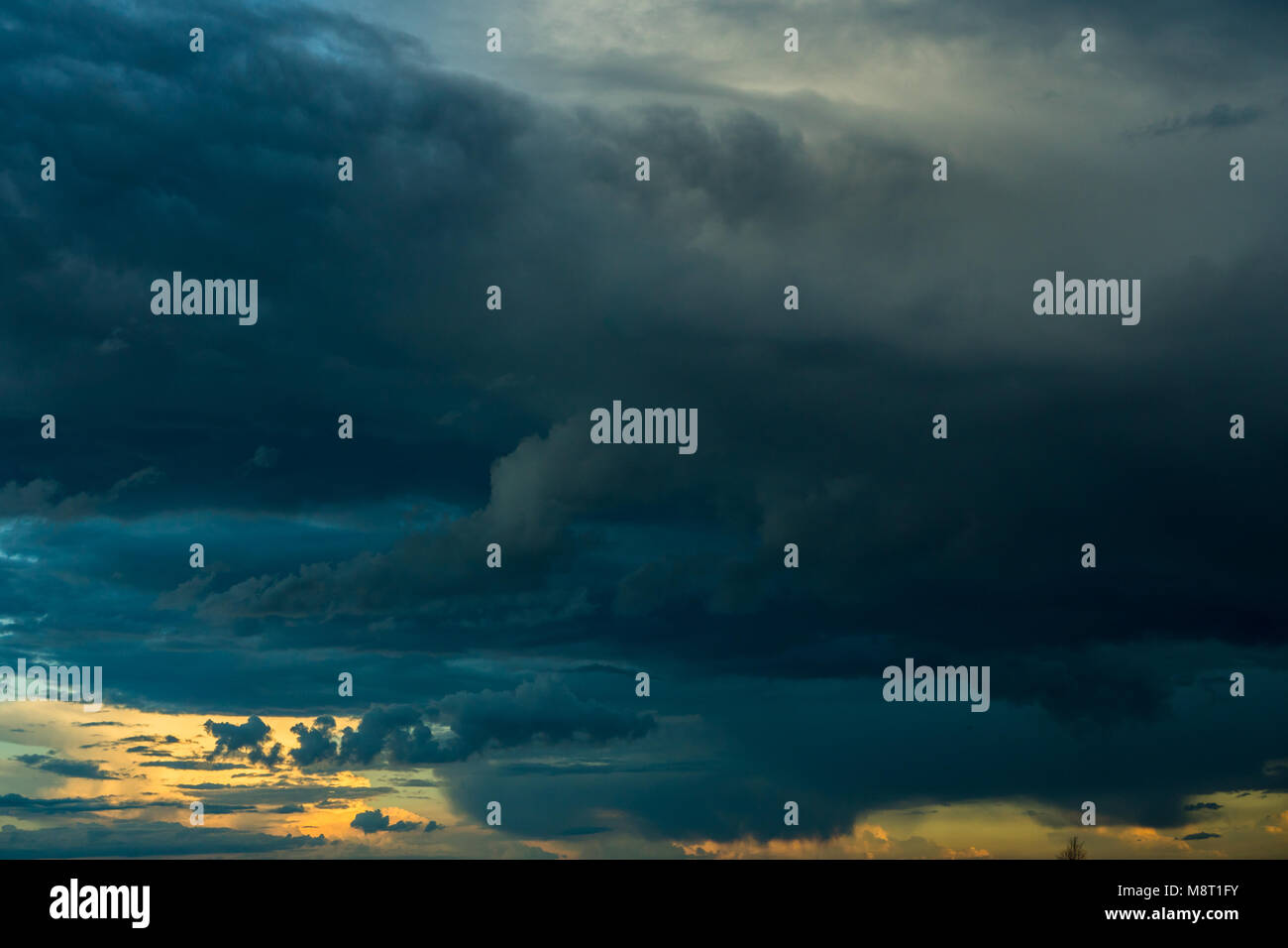 Overcast weather with stratus, cumulus and cumulonimbus clouds during the rain with clear sky and sunset in the - Stock Image