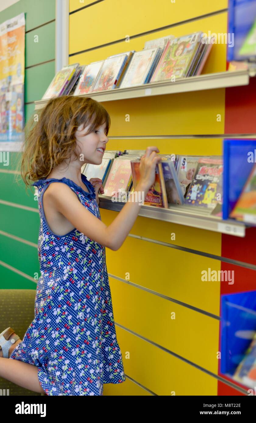 A young girl searches through DVDs at a public library, CityLibraries Aitkenvale, Townsville Queensland, Australia - Stock Image