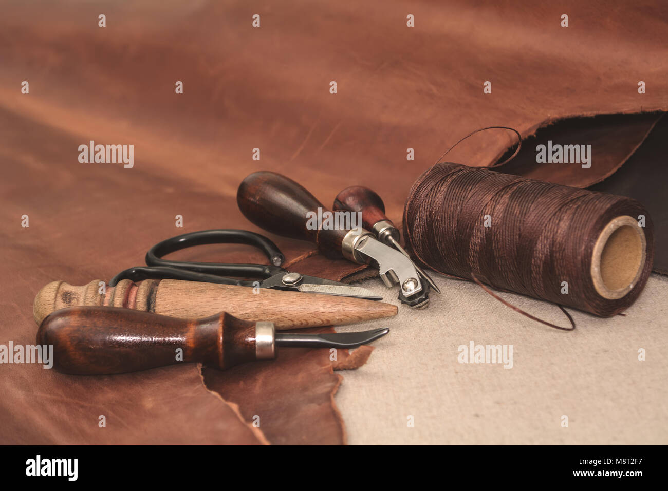 Tools for leather crafting and pieces of brown leather - Stock Image
