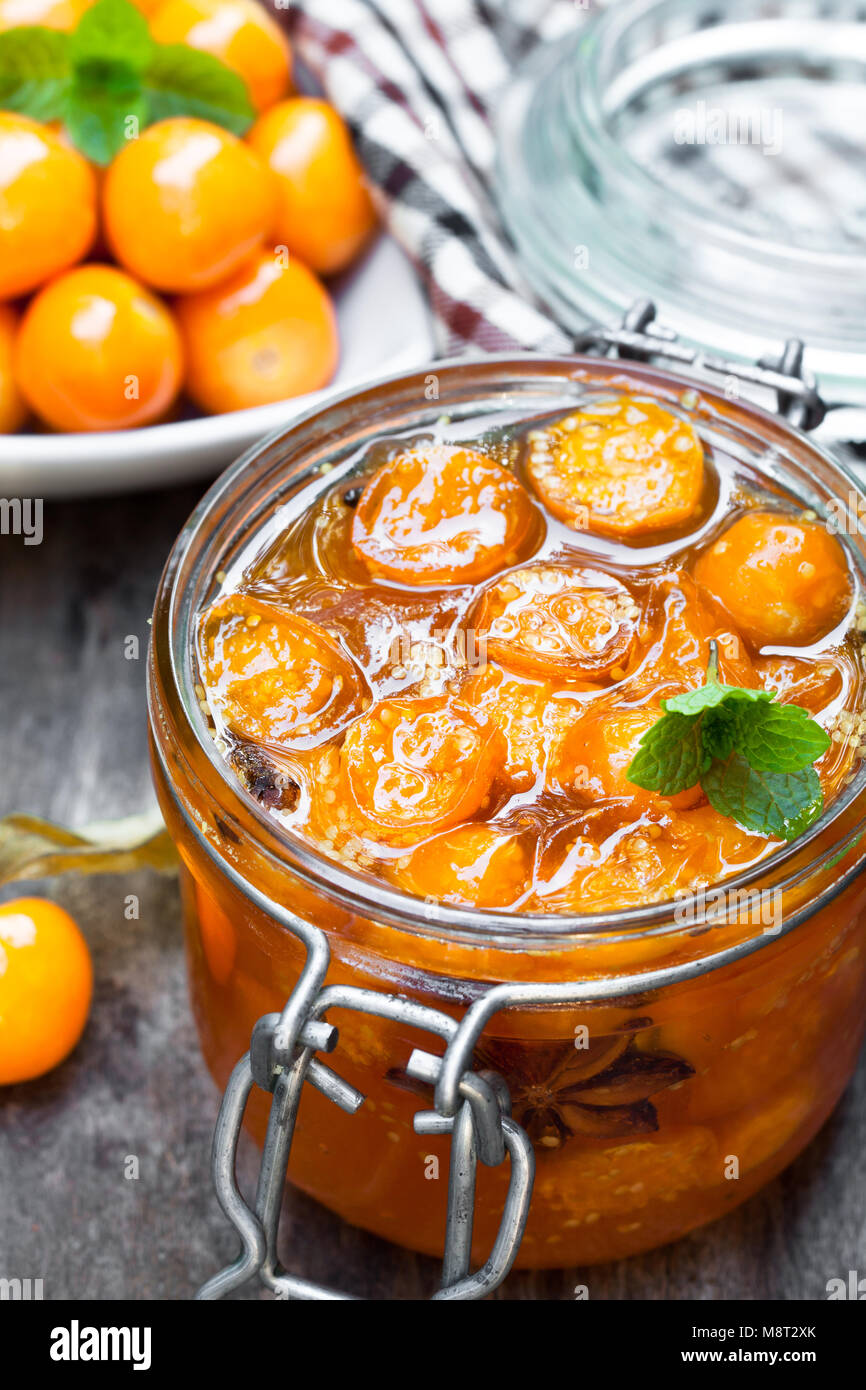 Homemade  physalis jam in jar on wooden table - Stock Image